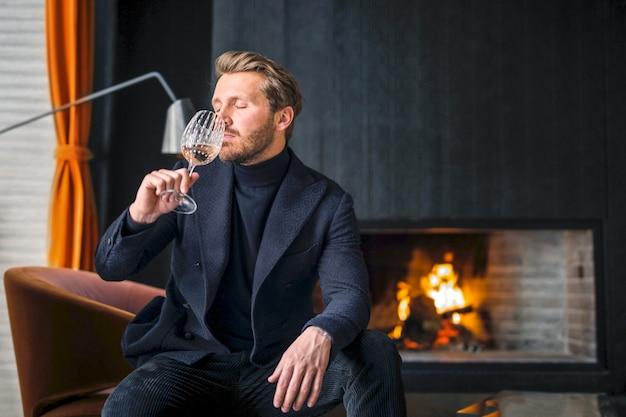 Uomo alla moda che beve un vino