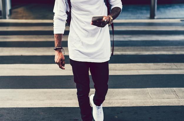Uomo alla moda che cammina attraverso la città