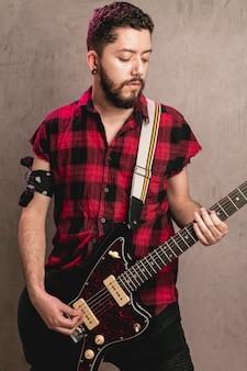 Uomo alla moda che gioca bella chitarra vecchia