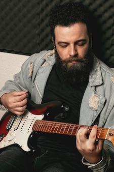 Uomo alla moda che gioca chitarra elettrica