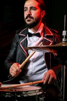 Uomo alla moda che gioca sul set di batteria