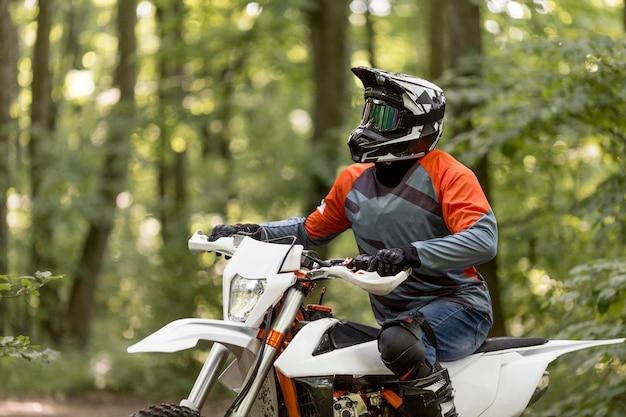 Uomo alla moda che guida una motocicletta nella foresta