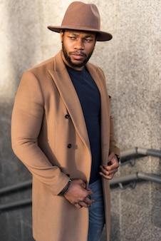 Uomo alla moda che indossa bei vestiti e un cappello