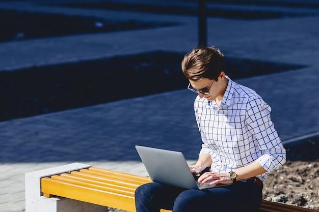 Uomo alla moda che lavora al computer portatile in strada