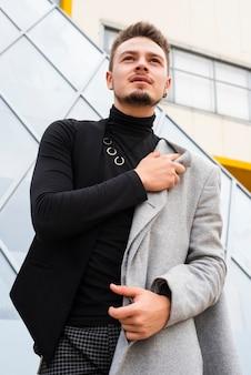 Uomo alla moda che osserva a partire dalla macchina fotografica