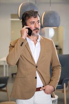 Uomo alla moda che parla sul telefono