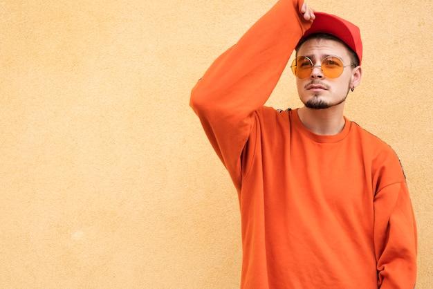 Uomo alla moda che posa sul fondo normale