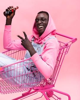 Uomo alla moda che propone in un carrello della spesa
