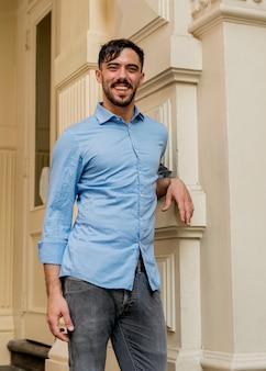Uomo alla moda che si appoggia sulla parete all'aperto