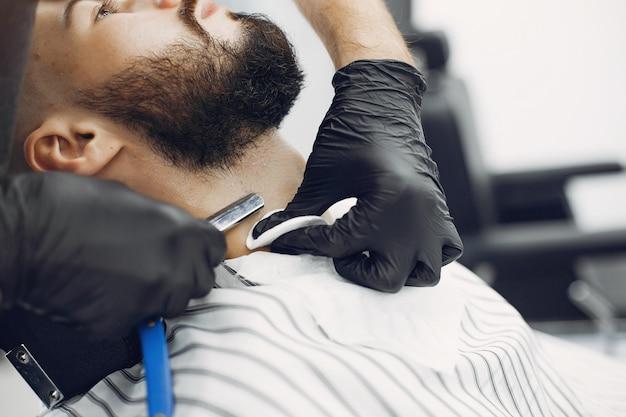 Uomo alla moda che si siede in un barbiere