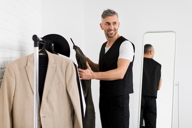 Uomo alla moda che tiene i vestiti e guardando lontano