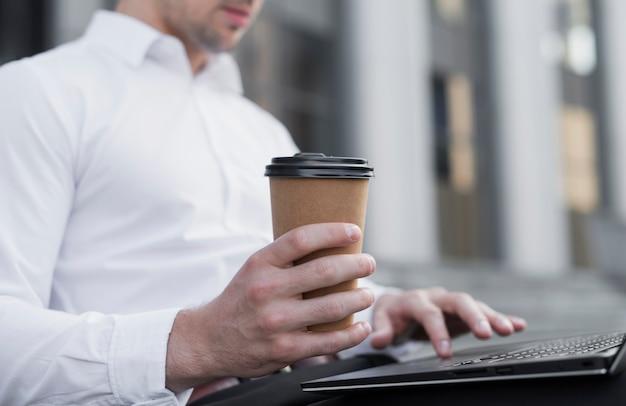 Uomo alla moda che tiene tazza di caffè