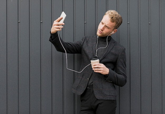 Uomo alla moda con caffè che prende un selfie