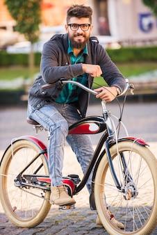 Uomo alla moda con gli occhiali cavalca una bicicletta.