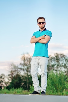 Uomo alla moda con le braccia incrociate che indossa polo blu su una strada deserta