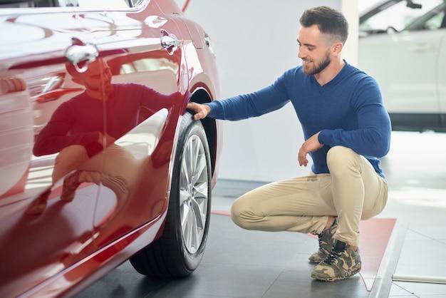 Uomo alla moda con taglio di capelli moderno accovacciato vicino auto di lusso.