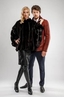 Uomo alla moda e donna di fascino in pelliccia che posa con l'attrezzatura di inverno.