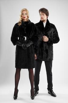 Uomo alla moda e donna di fascino nella posa della pelliccia