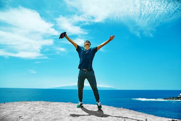 Uomo alla moda felice in abbigliamento casual che sta sulla scogliera della montagna