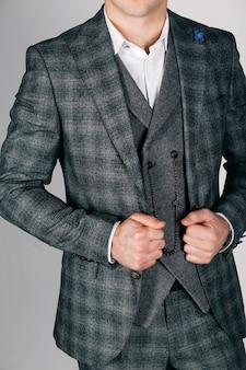 Uomo alla moda in abito a scacchi su grigio