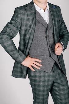 Uomo alla moda in abito a scacchi su uno sfondo grigio