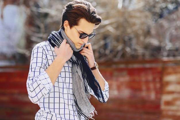 Uomo alla moda in camicia e occhiali da sole sulla strada urbana suuny