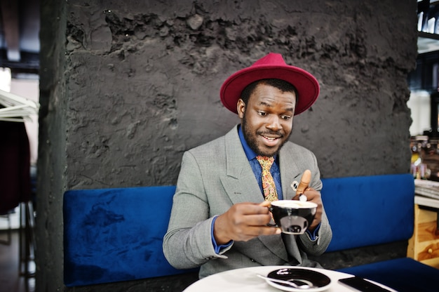 Uomo alla moda in cravatta grigia giacca e cappello rosso bere caffè al caffè