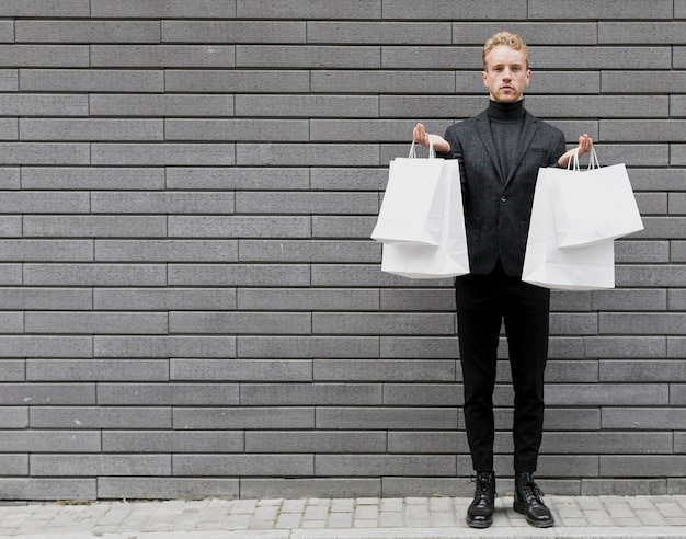Uomo alla moda in nero con borse della spesa bianche