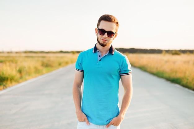 Uomo alla moda in polo blu che tiene la mano in tasca