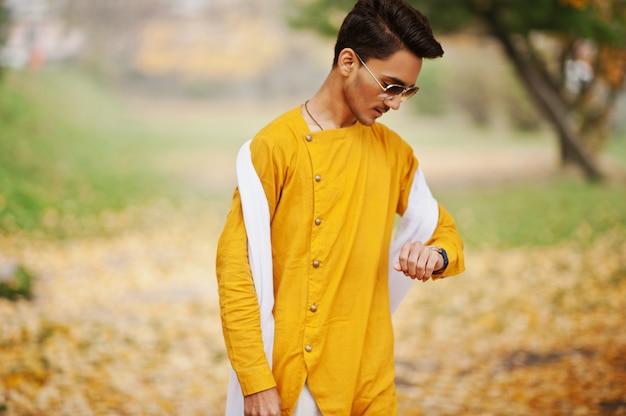 Uomo alla moda indiano in vestiti tradizionali gialli con la sciarpa bianca, occhiali da sole posti all'aperto contro l'albero delle foglie di autunno che esamina i suoi orologi.