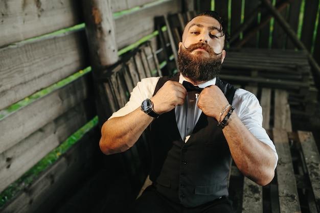 Uomo alla moda ponendo la cravatta a farfalla