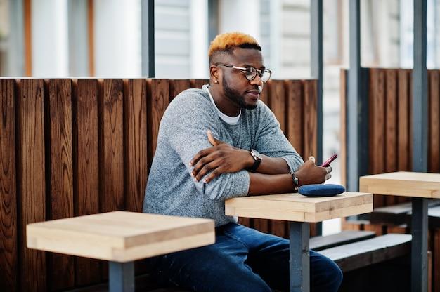 Uomo alla moda sul maglione grigio e occhiali posati in strada seduto sul tavolo in legno con caffè cellulare