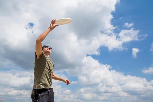 Uomo allegro che cattura il disco di plastica