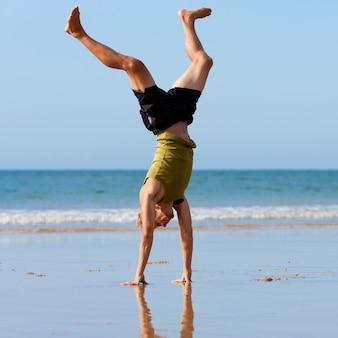 Uomo allegro che fa ginnastica sulla spiaggia