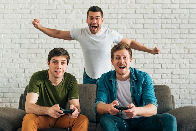 Uomo allegro che incoraggia per gli amici che giocano video gioco a casa