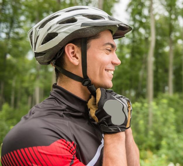 Uomo allegro che indossa il suo casco sportivo e distogliere lo sguardo.