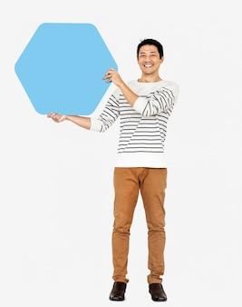 Uomo allegro che mostra un bordo esagonale blu in bianco