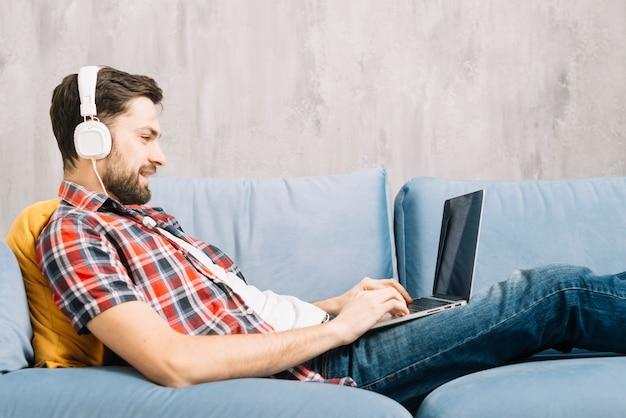 Uomo allegro che per mezzo del computer portatile e ascoltando musica