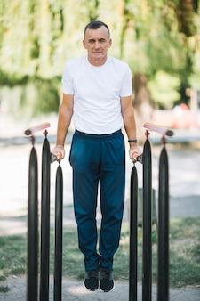 Uomo allegro che si esercita nel parco