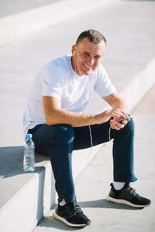 Uomo allegro che si siede con uno smartphone in sue mani