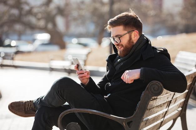 Uomo allegro che si siede e che utilizza smartphone nella città