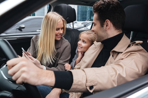 Uomo allegro che si siede in automobile con sua moglie e figlia