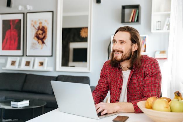 Uomo allegro che si siede nella tavola facendo uso del computer portatile a casa