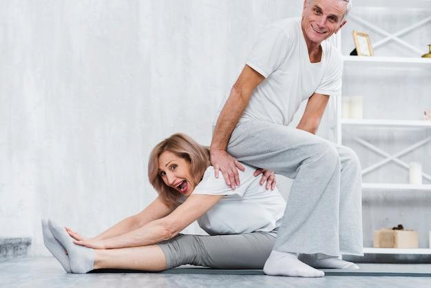 Uomo allegro che si siede sulla parte posteriore di sua moglie mentre facendo yoga a casa