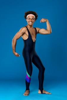 Uomo allegro che sorride, che posa, che mostra i muscoli
