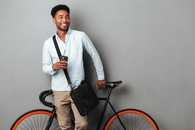 Uomo allegro che sta bicicletta vicina isolata
