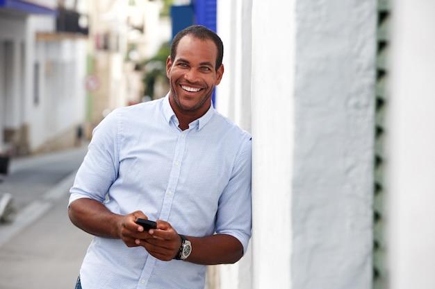 Uomo allegro che sta fuori sulla strada con il telefono cellulare