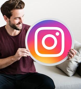 Uomo allegro che tiene un'icona di instagram