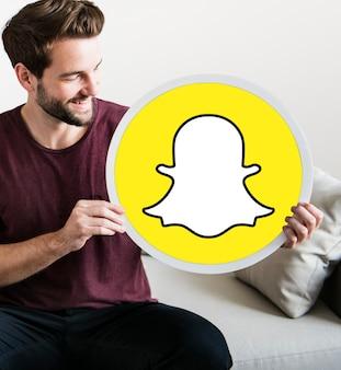 Uomo allegro che tiene un'icona snapchat