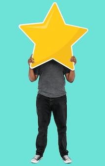 Uomo allegro che tiene un simbolo di valutazione della stella dorata